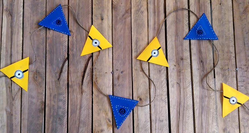 Eine Minion-Girlande ist ganz einfach aus gelben und blauen Wimpel gebastelt.