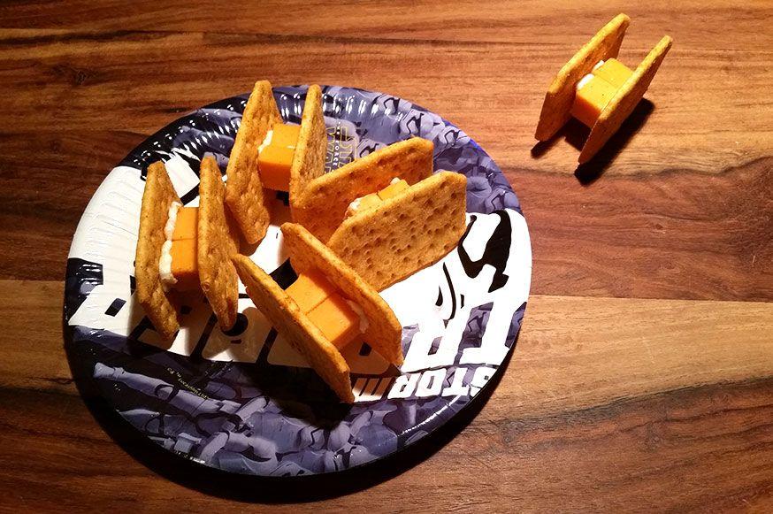 Mit Crackern und Käsewürfeln lassen sich die coolen TIE-Fighter für die Star Wars Party basteln.
