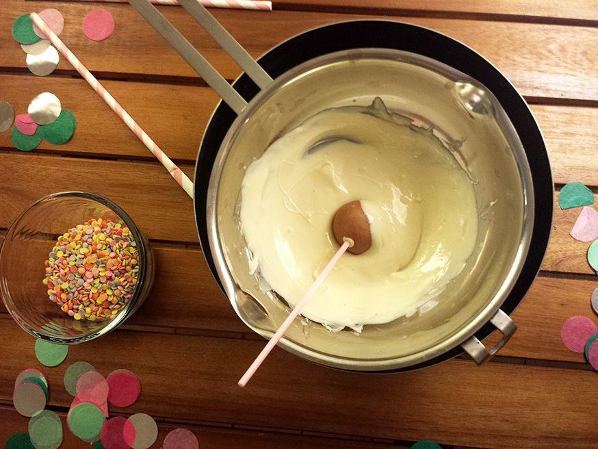 Am besten geben Sie die Zuckerstreusel in eine Schüssel, in welche Sie die Schokokugel tauchen. So verteilen sich die Streusel gleichmäßig.